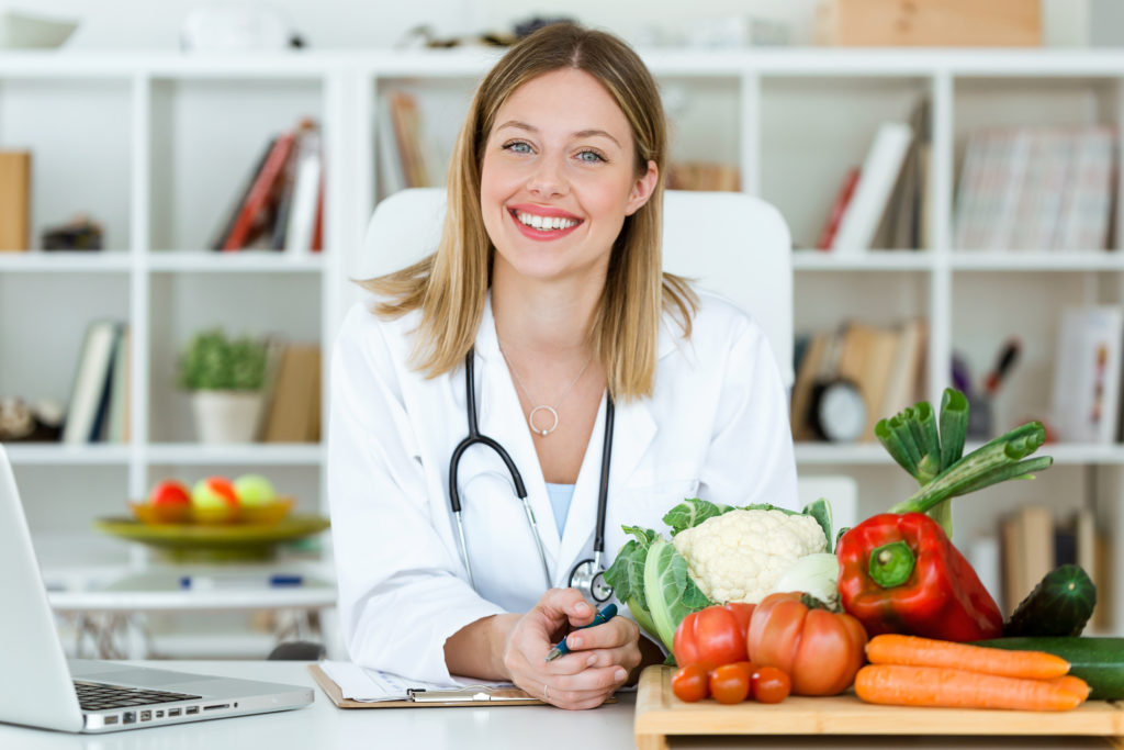 Portrait of smiling nutritionist looking at camera and showing healthy vegetables in the consultation.
