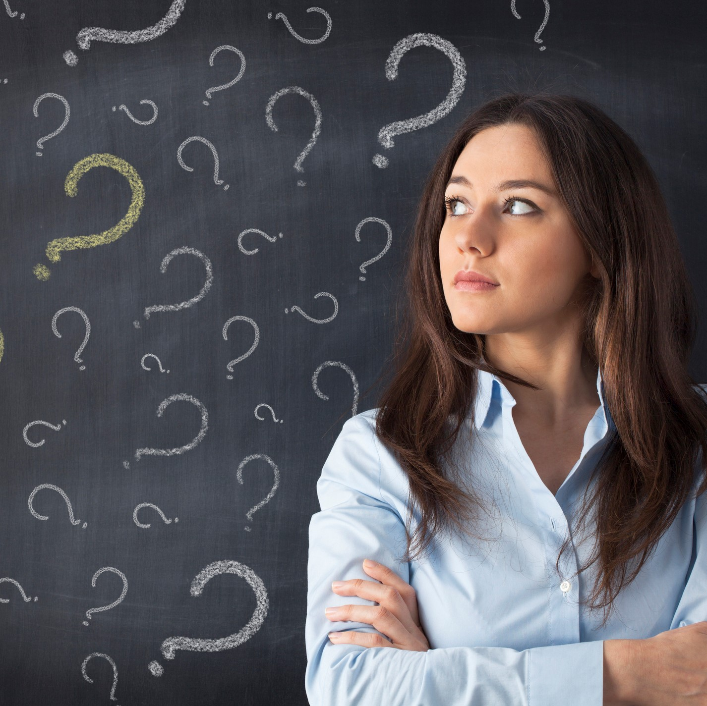 Woman in front of question marks drawn on blackboard