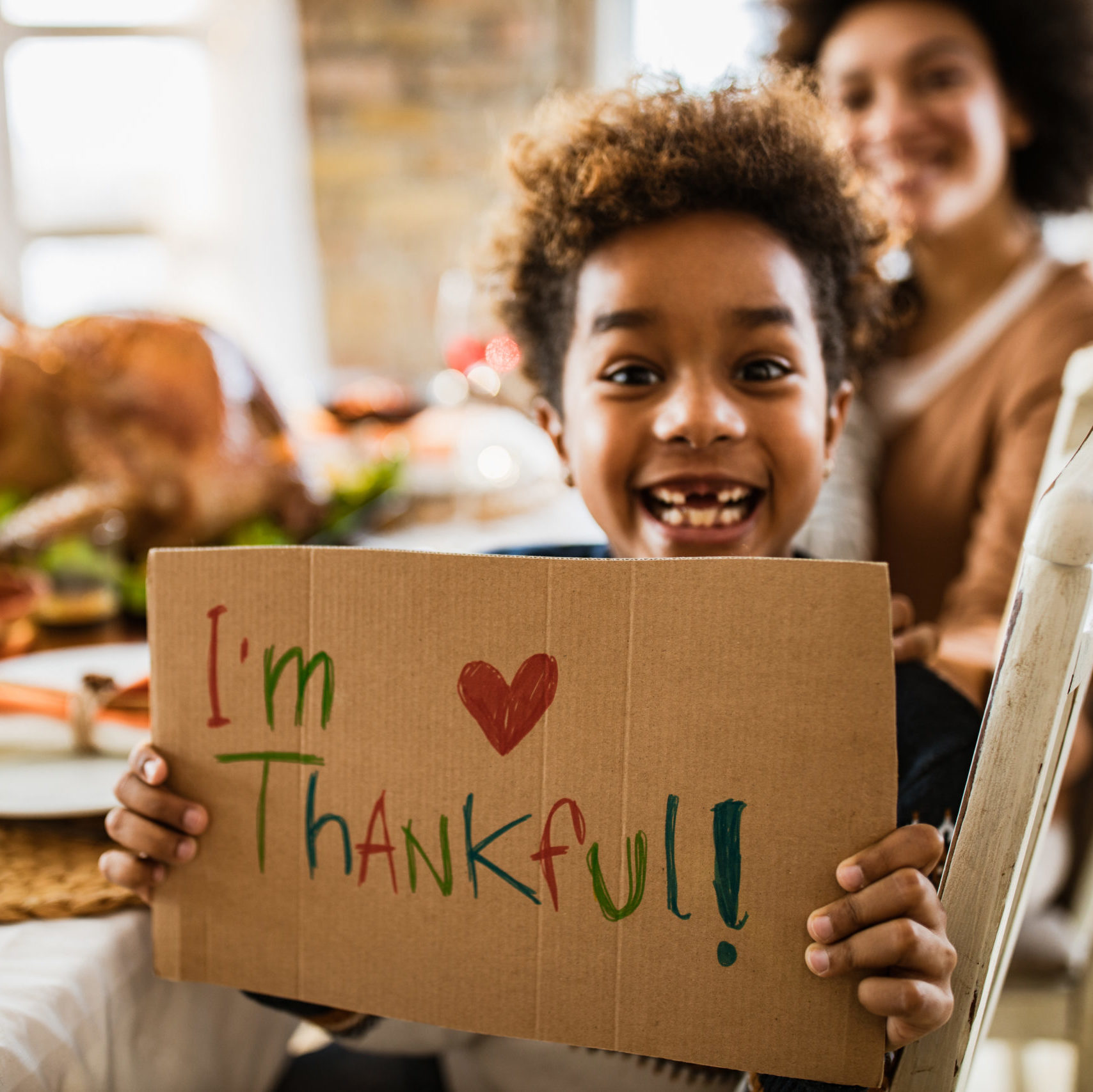 Happy African American girl holding 'I'm thankful' sign and looking at camera during Thanksgiving meal with her parents.